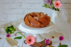 Hier kannst du einen zuckerfreien Schoko - Nuss Gugelhupf von vorne fotografiert sehen. Der Gugelhupf wurde mit Blumen und einem alten Tortenheber schön angerichtet.