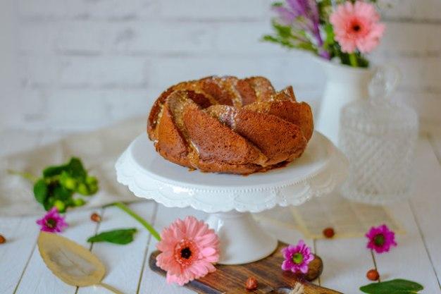 Auf dem Bild ist ein zuckerfreier Schoko - Nuss Gugelhupf zu sehen. Um den Gugelhupf herum liegt ein alter Tortenheber und im Hintergrund steht ein Blumenstrauß.