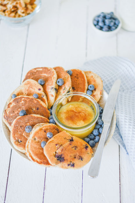 Zuckerfreie Heidelbeer Pancakes liegen auf einem Teller und in der Mitte eine Schüssel mit Apfelmus und Zimt. Das Pancakes Teller steht auf einem weißen Vintage Holzdielentisch.