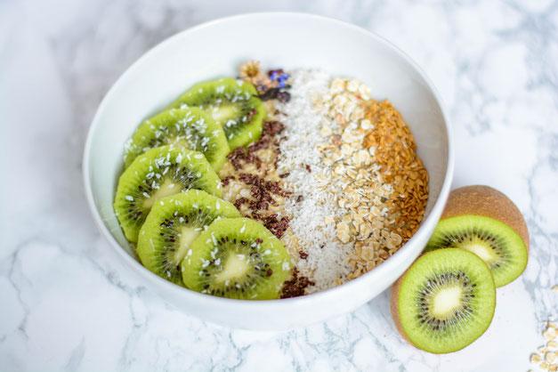 Auf diesem Bild ist eine Kiwi - Haferflocken Frühstücksbowl z u sehen, die von oben fotografiert wurde. Die Frühstücksbowl steht auf einer weißen Marmorplatte.
