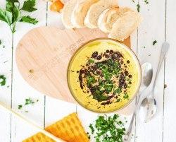 Hier ist eine asiatische Kürbis - Cremesuppe zu sehen. Die Suppe wurde von oben fotografiert und die Suppenschüssel steht auf einem herzförmigen Holzbrett. Daneben liegt frisches Baguette und frische Kräuter.