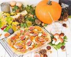 Auf dem Bild ist ein herbstlicher Flammkuchen zu sehen. Der Flammkuchen ist mit Kürbis, Feigen, Maroni und Walnüssen belegt.
