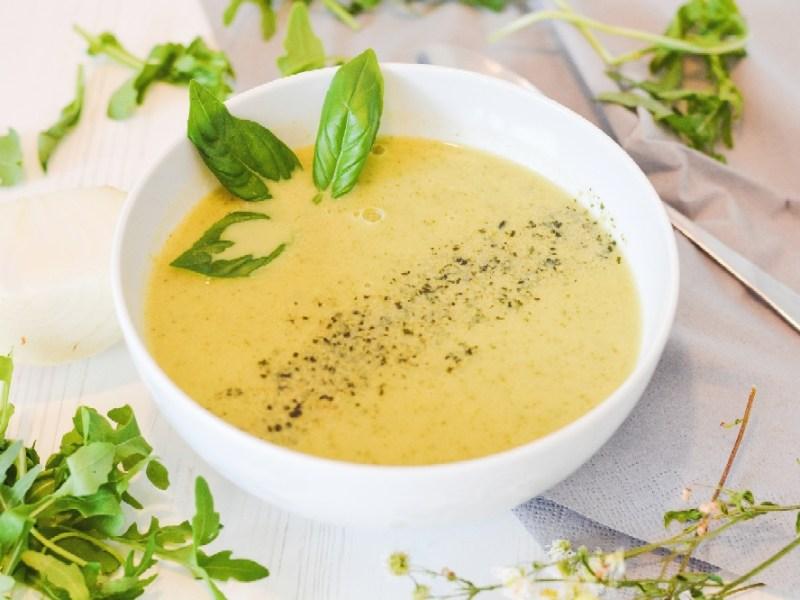 Auf diesem Bild ist eine warme Gurkensuppe zu sehen. Die Suppe wurde von oben fotografiert und mit vielen frischen Kräutern dekoriert. Im Hintergrund liegt ein graues Geschirrtuch.