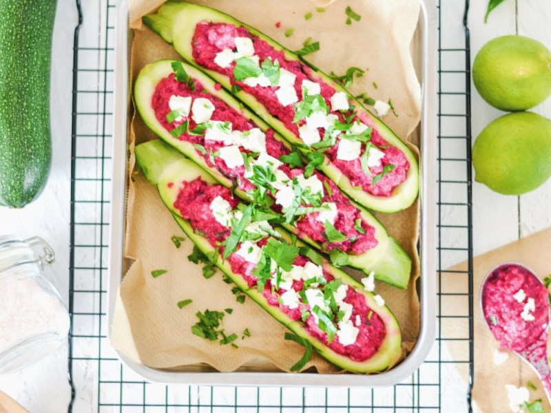 Gefülle Zucchini Schiffchen mi roter Beete und Feta von oben fotografiert. Die Zucchini Schiffchen liegen in einer Auflaufform welche auf einem schwarzen Backgitter steht.