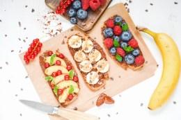 Hier sind Brote mit zuckerfreiem Nutella und frischem Obst zu sehen. Die Brote wurde von oben fotografiert, daneben liegt ein Messer.