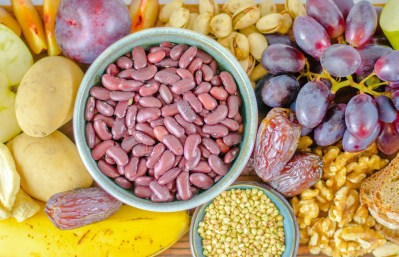 Hier sind viele Lebensmittel zu sehen, welche von oben fotografiert wurden. Es sind Lebensmittel, die viele Ballaststoffe beinhalten wie Kartoffeln, Weintrauben, Nüsse und Banane.