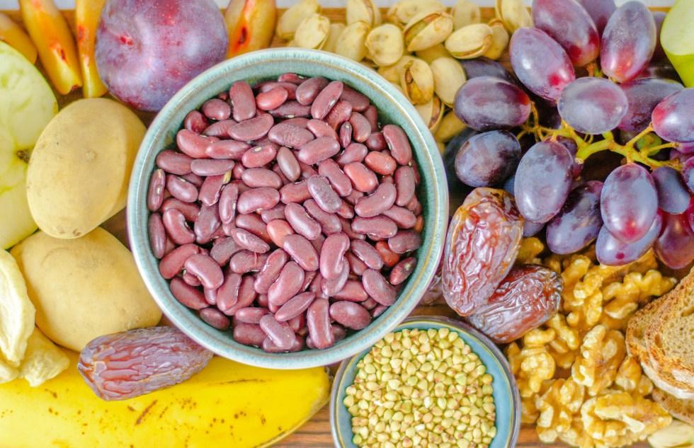 Auf diesem Bild siehst du unterschiedliche Lebensmittel von oben fotografiert, die viele Ballaststoffe beinhalten. Du siehst hier Weintrauben, Kidneybohnen, Datteln, Walnüsse, Bananen, Äpfel und Kartoffeln.