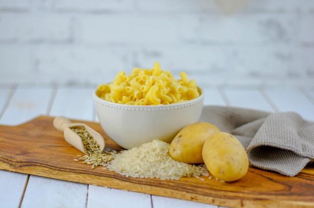Auf diesem Bild sind mehrere Lebensmittel zu sehen, in denen resistente Stärke enthalten ist. Unter anderem sind hier Teigwaren, Getreide, Reis und Kartoffeln zu sehen.