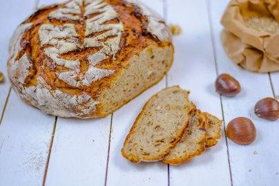 Auf diesem Bild sieht man ein Maroni - Walnuss Brot. Es liegt auf alten weißen Holzdielen und im Hintergrund liegen Maroni und frisches Getreide.