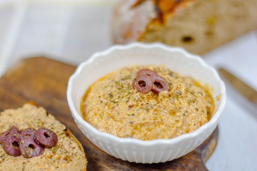 Mediterraner Olivenaufstrich von schräg oben fotografiert. Im Hintergrund ist ein frisch gebackenes Brot zu sehen.