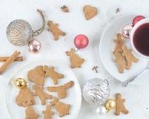 Hier ist zuckerfreier Lebkuchen zu sehen. Daneben steht eine Tasse Früchtetee und kleine Christbaumkugeln.