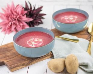 Rote Rüben Suppe von vorne fotografiert. Im Vordergrund liegen zwei Kartoffeln und im Hintergrund Blumen.