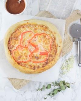 Hier ist eine selbstgemachte Pizza zu sehen, die auf einem großen alten Holzbrett liegt. Daneben liegt ein Pizzaroller und eine Schüssel mit Tomatensoße.