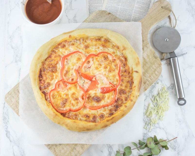 Bei diesem Rezept kannst du eine Pizza fu einem Holzbrett sehen. Es wurde von oben fotografiert. Links davon steht die Tomatensoße und rechts davon liegt ein Pizzaroller.