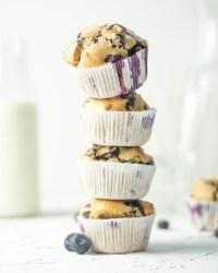 Auf diesem Bild sind zuckerfreie Heidelbeeren Muffins zu sehen. Sie sind übereinander gestapelt. Im Hintergrund steht eine Flasche mit frischer Milch und daneben liegen frische Heidelbeeren. Der Hintergrund ist weiß und schlicht gehalten.