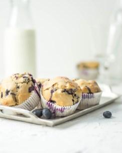 Diese Heidelbeer Muffins wurden von vorne fotografiert. Die Muffins liegen auf einem silbernen Tablett und im Hintergrund steht eine Flasche mit Milch.