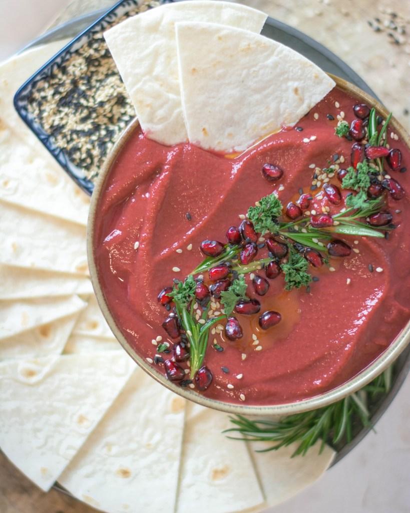 Auf dem Bild ist ein rote Beete Hummus zu sehen. Im Hummus stecken zwei Tortillastücke.