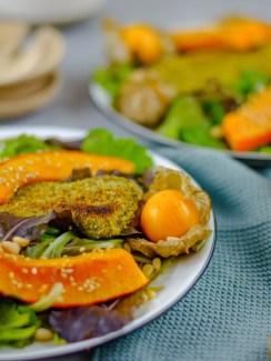 Auf diesem Bild ist ein zucchini in kürbiskernpanade und in sesam gebratenem kürbis mit gemischten salat zu sehen. Das Gemüse liegt auf einem weißen Teller und daneben ein blaues Geschirrtuch.