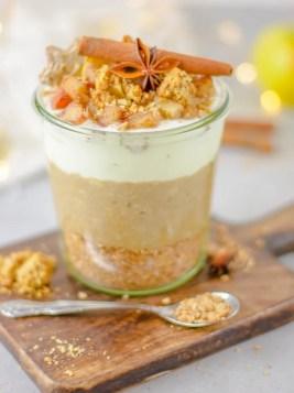 Auf diesem Bild ist ein zuckerfreier Bratapfel - Spekulatius Porridge zu sehen. Der Porridge wurde von vorne fotografiert und steht auf einem Holzbrett. Im Hintergrund sind Lichter zu sehen.