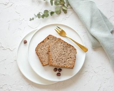 Ein zuckerfreier Nusskuchen auf einem weißen Teller wurde von oben fotografiert. Der Nusskuchen liegt auf einem weißen Teller und daneben liegt eine goldene Gabel und frische Haselnüsse.