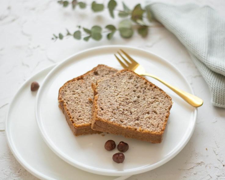 Auf diesem Bild ist ein zuckerfreier Nusskuchen zu sehen. Der Nusskuchen liegt auf einem weißen Dessertteller und daneben liegt eine goldene Gabel.