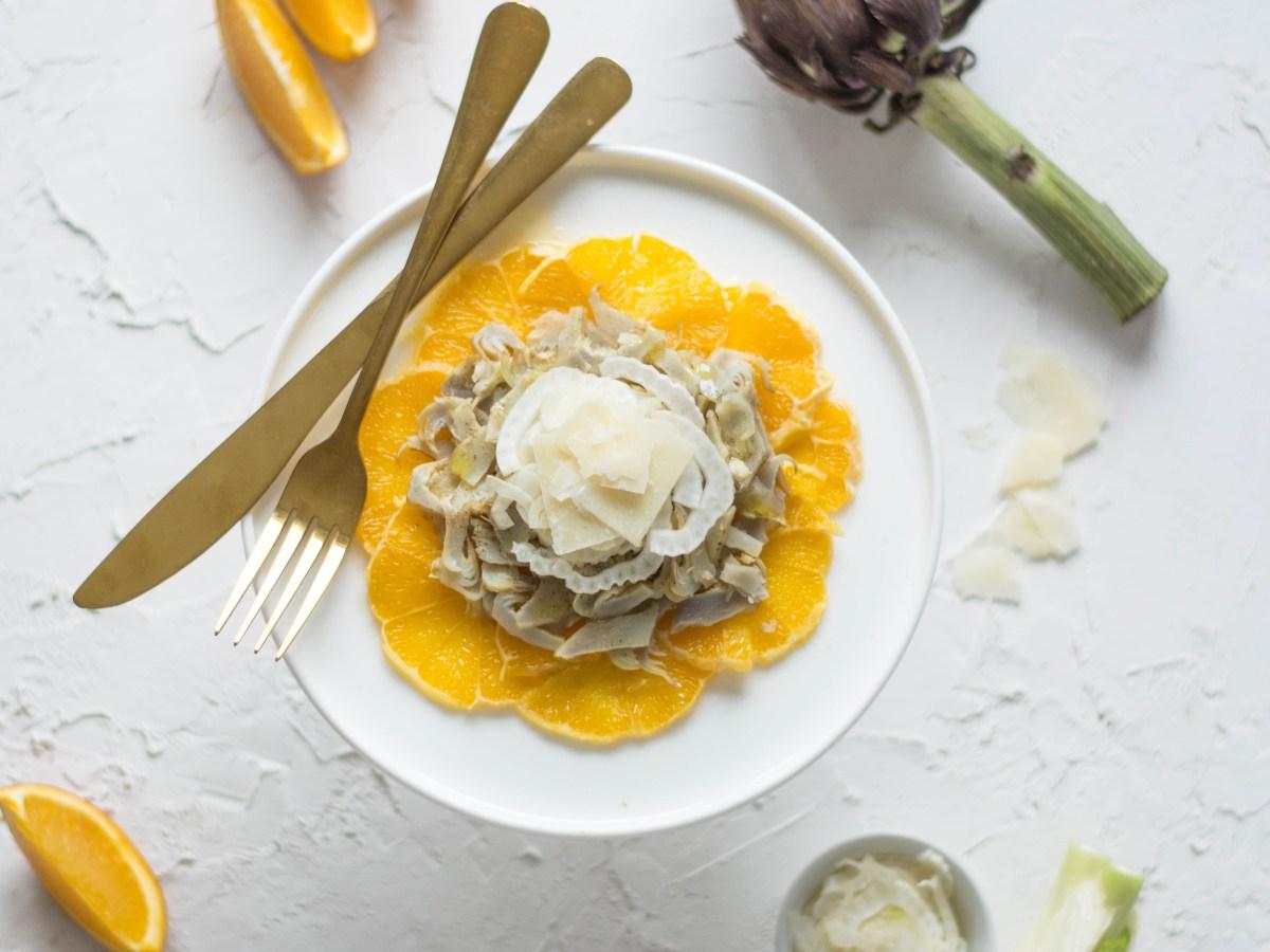 Ein Orangen - Artischocken Carpaccio auf einem weißen Teller fotografiert. Neben dem Carpaccio liegt eine goldene Gabel und ein goldenes Messer. Daneben kann man die Grundzutaten, Fenchel, Orange, Fenchel und Parmesan erkennen.