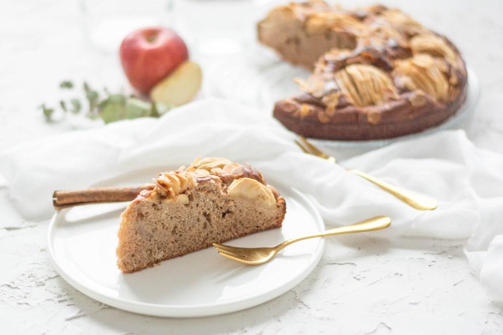 Auf diesem Bild ist ein zuckerfreier und veganer Dinkel - Apfelkuchen von vorne fotografiert zu sehen. Im Hintergrund liegt ein Apfel und zwei goldene Gabeln.