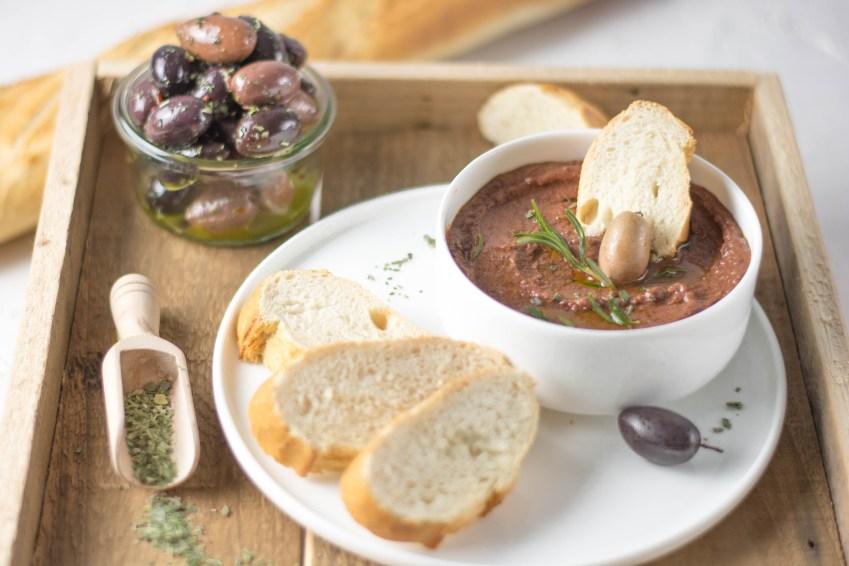 Auf diesem Bild sieht man die beste griechische Olivenpaste von vorne fotografiert. Die Olivenpaste ist schön angerichtet in einer weißen Schüssel. Im Hintergrund sieht man marinierte Oliven stehen und ein angeschnittenes Baguette liegt daneben.