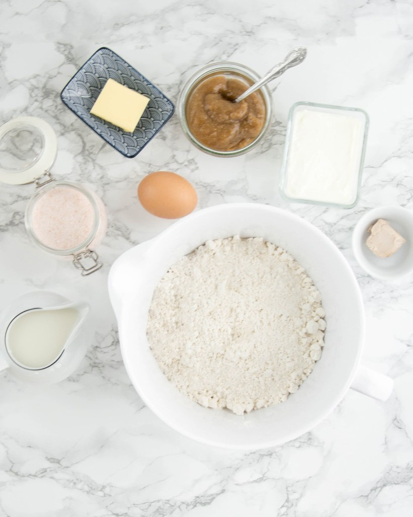 Hier ist eine Marmor Arbeitsplatte zu sehen mit vielen Zutaten. Mein zuckerfreier Brioche Osterkranz benötigt diese Zutaten um so herrlich zu schmecken.