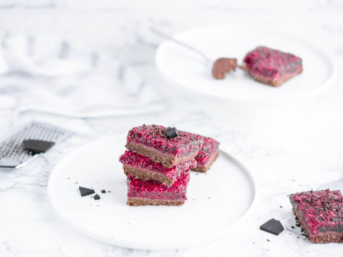 """Auf diesem Bild ist ein zuckerfreier """"no bake"""" Himbeer - Schoko Kuchen zu sehen. Im Hintergrund liegt eine Gabel und ein Stück Schokolade. Das Bild wurde von vorne fotografiert."""