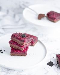 """Hier ist ein zuckerfreier """"no bake"""" Himbeer - Schoko Kuchen zu sehen. Der Kuchen liegt auf einem weißen Teller und daneben liegen gebrochene Stücke Schokolade."""