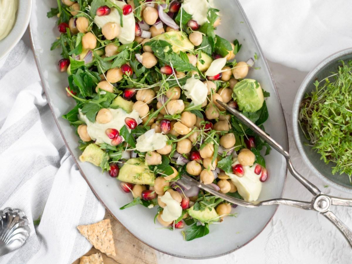Auf diesem Bild ist ein schneller Kichererbsen Salat zu sehen. Der Salat wurde auf einem hellblauen Servierteller serviert und daneben steht eine Schüssel mit frischer Kresse.