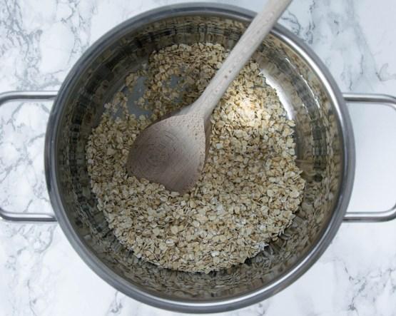 Ein Kochtopf wurde von oben fotografiert. In dem Kochtopf befinden sich Haferflocken und ein Kochlöffel. Die Haferflocken werden für den Porridge geröstet.