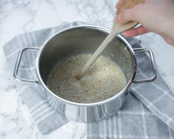 Für diese Frühstücksideen auf dem Bild ist es besonders wichtig, mit der Rückseite des Kochlöffels umzurühren, damit sich bei dem Porridge keine Klumpen bilden. Man kann einen Kochtopf, den Porridge, ein Geschirrtuch und einen Kochlöffel sehen.