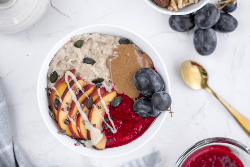 Auf diesem Bild ein Porridge zu sehen für die Anleitung für gesunde Frühstück. Ein cremiger Porridge der mit Nektarinen, Mandelmus und Himbeersoße angerichtet wurde.
