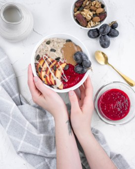 Auf diesem Bild sieht man einen Haferbrei, der mit zwei Händen gehalten und auf einen Früshtückstisch gestellt wird. Daneben liegt ein Geschirrtuch, eine Schüssel mit Nüssen und eine Milchkanne steht davor.