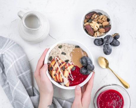 Auf diesem Bild kannst du die Bildanleitung für einen Haferbrei sehen. Dieser wurde als gesundes Frühstück in einer weißen Müslischüssel angerichtet und wird mit zwei Händen auf den Frühstückstisch gehoben.