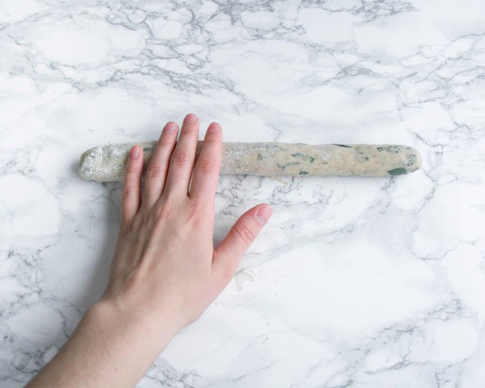 Auf diesem Bild kannst du einen Teigling von oben fotografiert sehen, der mit der Hand zu einer langen Schlange geformt wird. Aus diesem Teigstück wird später ein Bärlauch - Knoten Brötchen geformt.