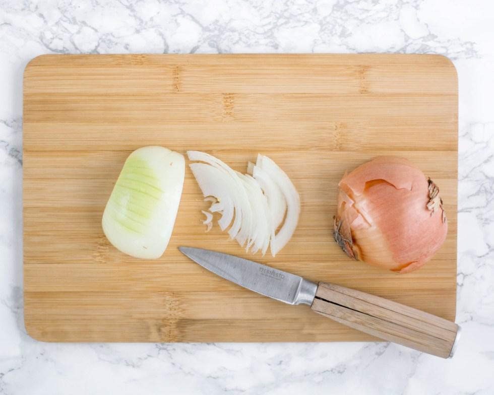 Ein Bild von einer Zwiebel von oben fotografiert. Die Zwiebel wird auf dem Bild mit einem Messer in dünne Scheiben schneiden.