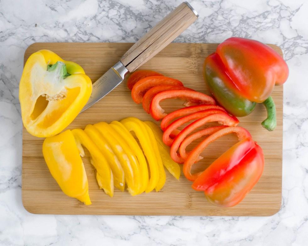 Auf diesem Bild kann man eine gelbe und rote Paprika auf einem Holzbrett zu sehen. Die Paprika wird mit einem scharfen Messer in dünne Streifen geschnitten.