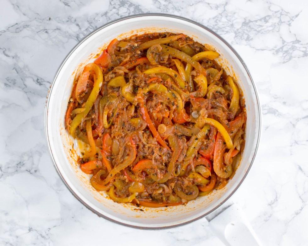 Auf diesem Bild ist zu sehen, wie für das Ratatouille aus dem Ofen die Paprika in einer Pfanne mit Tomatenmark und Gewürzen angebraten wird.