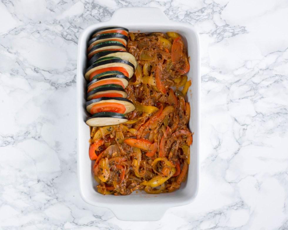 Hier sieht man die Melanzani, die Zucchini und die Tomaten wie sie nacheinander immer in derselben Reihenfolge auf der Paprika - Zwiebel Mischung in einer Auflaufform geschichtet werden.