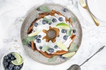 Ein zuckerfreier Heidelbeer - Limetten Gugelhupf von oben fotogarfiert. Der Gugelhupf liegt auf einem Hand getöpferten Teller und daneben liegen Dessertteller, eine goldene Dessertgabel und eine Gebäckzange. Verziert ist der Kuchen mit Heidelbeeren, Limetten und Eukalyptusblättern.