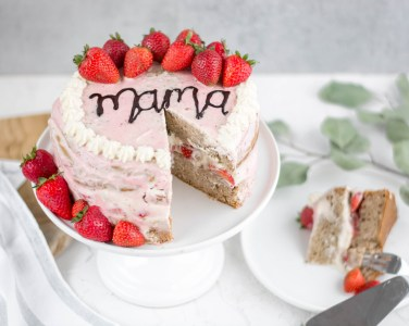 Hier kannst du eine zuckerfreie und vegane Muttertagstorte sehen. Die Erdbeertorte wurde mit frischen Erdbeeren und einer Erdbeercreme verziert. Sie wurde bereits angeschnitten und man sieht die Creme und die Erdbeerstücke im Inneren.
