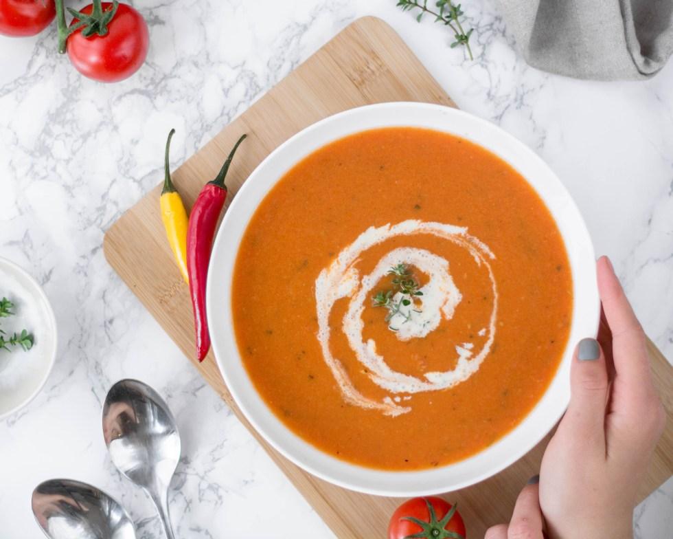 Auf diesem Bild ist eine geröstete Tomatensuppe zu sehen. Die geröstete Tomatensuppe wurde von oben fotografiert und daneben liegen frische Tomaten und Chilis.