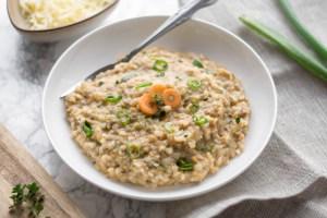 Auf diesem Bild ist ein herzhafter Buchweizen Porridge zu sehen, welcher in einer weißen Schüssel schön angerichtet wurde mit frischen Kräutern, Frühlingszwiebeln und Karotten. Daneben liegt ein Holzbrett und ein Geschirrtuch.