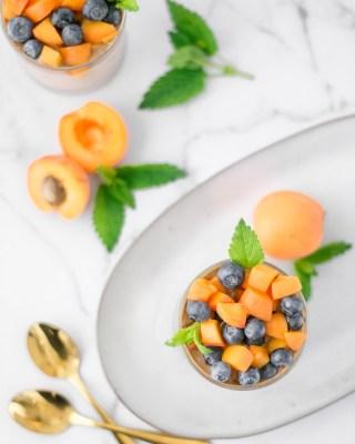 Dieser veganer Marillen - Mandel Porridge wurde von oben fotografiert und mit Marillen und Heidelbeeren angerichtet. Neben den beiden Porridge - Gläsern liegen frische Melissenblätter, Marillen und zwei goldene Löffel.