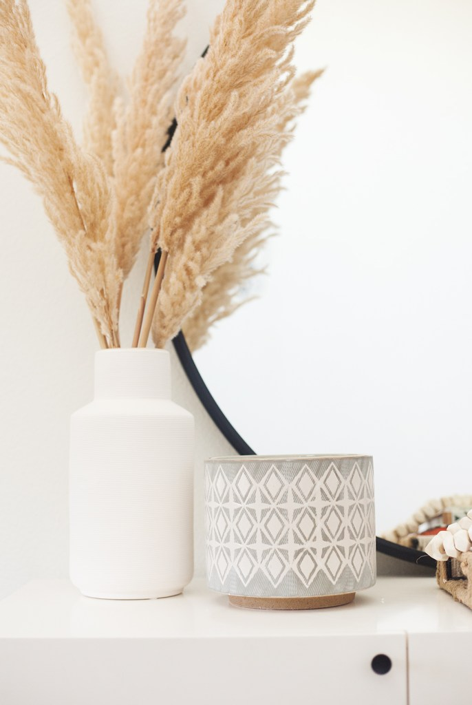 Vintage Chic Decor with Walmart by popular life and style blog, E. Interiors: image of a Walmart Urban Trends Collection: Ceramic Vase Coated Finish White with pompas grass in it and a Walmart 3R Studios Grey and White Stoneware Planters.