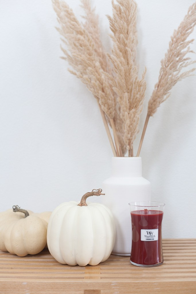 WALMART FALL DECOR by popular interior design blog, E. interiors: image of a red WoodWick candle, pompas grass in a white vase and 2 faux pumpkins.