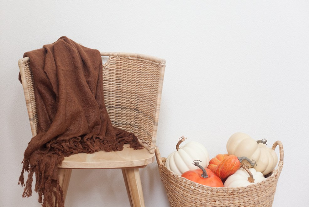 WALMART FALL DECOR by popular interior design blog, E. interiors: image of a bench with Better Homes & Gardens Feather Filled Banded Button Decorative Throw Pillow and a MoDRN Woven Faux Mohair Throw Blanket on it and a DecMode Woven Seagrass Basket With Braided Handles filled with pumpkins.